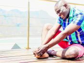 Man sitting on a deck holds his feet in pain